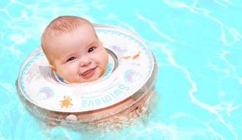 うきわ型スポーツ知育用品のスイマーバを装着する赤ちゃん